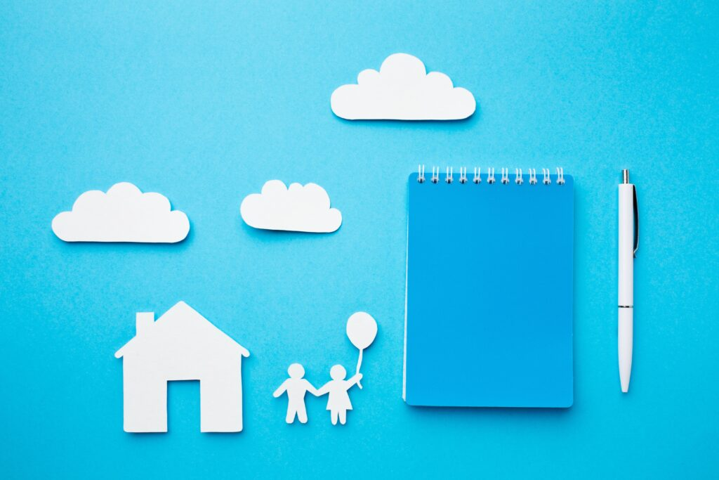 Cut outs of a house, two people with one holding a balloon and clouds on a blue background