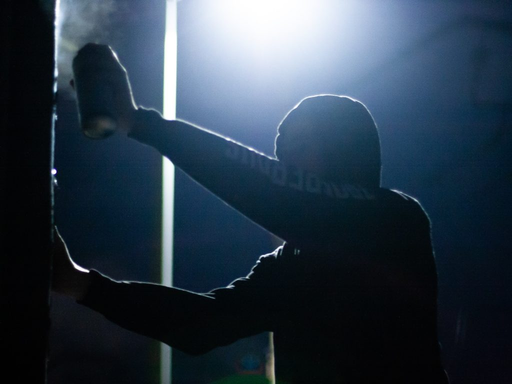 a silhouette of a person spray painting
