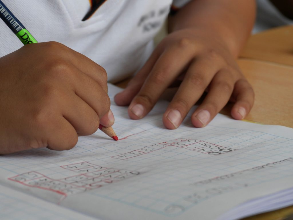 A photo showing the hands of a child doing maths work and holding a pencil